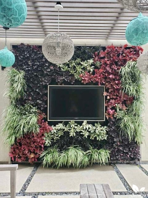 Outdoor living greenwall framed around a TV