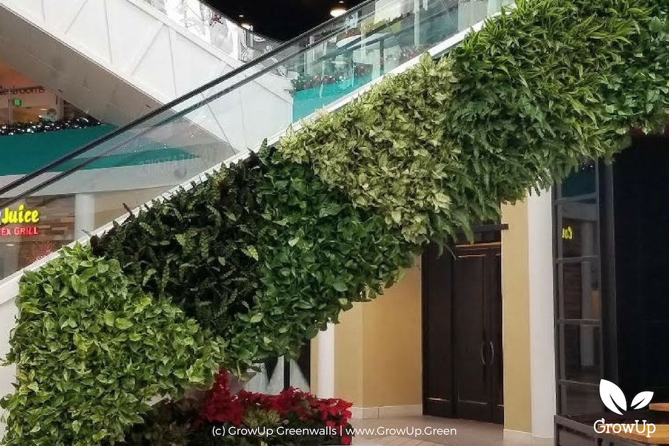 An escalator in a mall with a greenwall mounted on the side of it