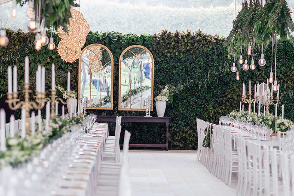A wedding reception area with long tables and the entire wall behind being a greenwall