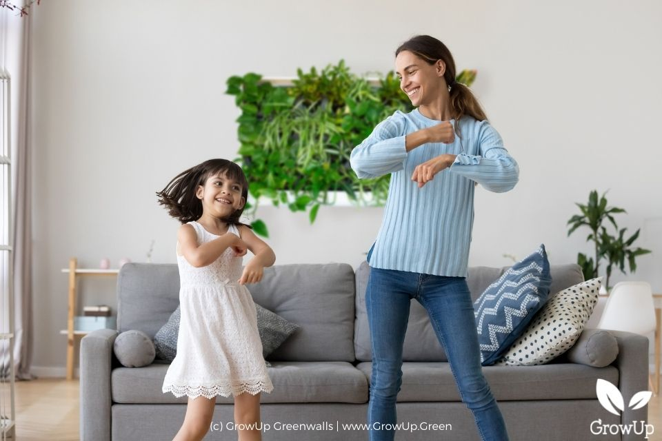 Mother and daughter dancing in their living room in front of a Freedom Series Designer pre-built greenwall.