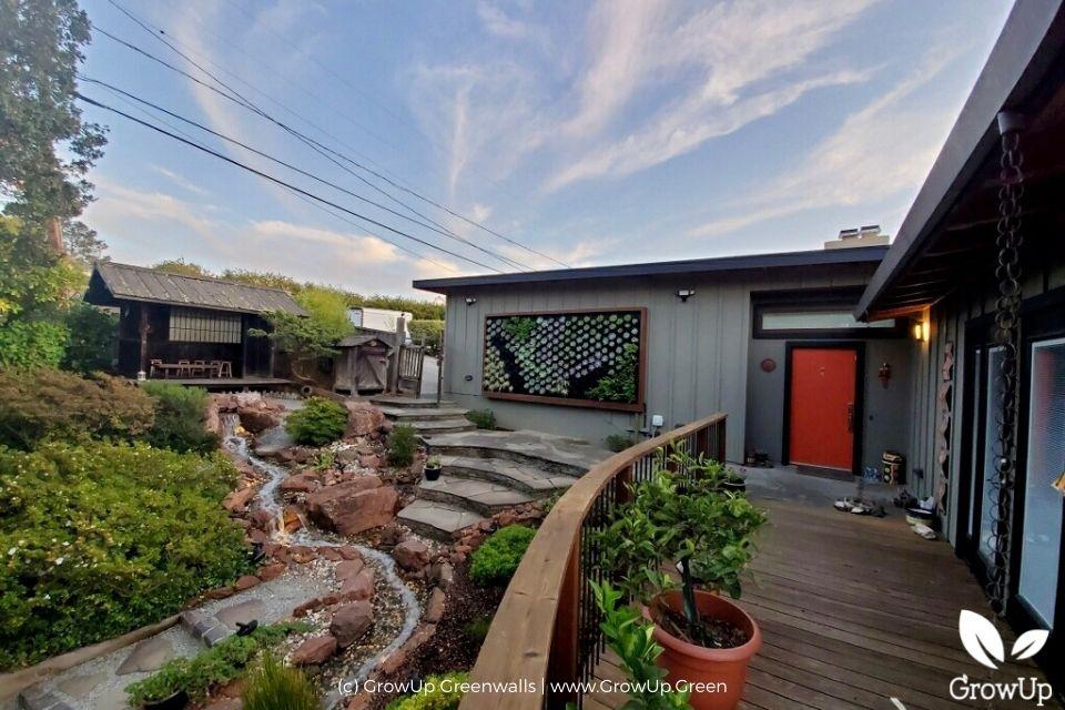 Eclectic style landscaped yard with a succulent wall.