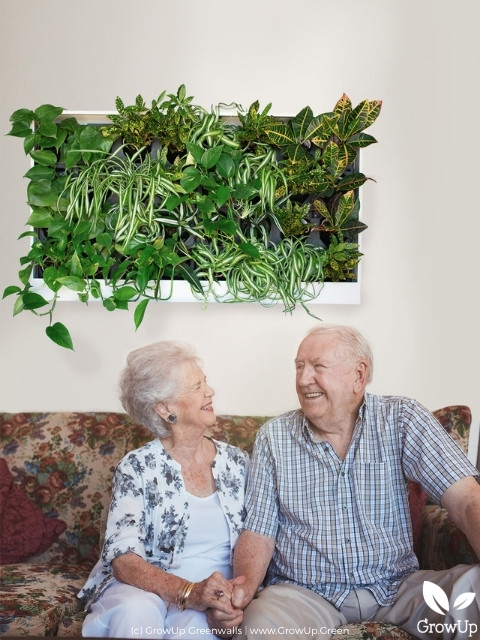 happy old couple sitting in front of freedom series designer greenwall